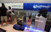 A young passenger waits on a Southwest Airlines scale as her family checks in at the adjacent Delta Air Lines desk at Dallas Love Field in Dallas on June 10, 2016.(Tom Fox/Staff Photographer)