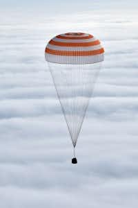 <p>Russia's Soyuz TMA-18M space capsule descended through the clouds above Kazakhstan.</p>(Krill Kudryavtsev/Associated Press)