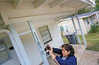 City of Dallas code inspector Diana Conde takes a photo of a repair that was done to the eaves as she conducts an inspection of a single-family home in the Hamilton Park area of North Dallas.(Louis DeLuca/Staff Photographer)