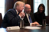 """President Donald Trump kisses a  """"postcard"""" tax return, part of the outline of the Republicans' just-released tax proposals, at the White House in Washington on Nov. 2, 2017. House Republican lawmakers outlined a $1.51 trillion tax plan that would deliver a significant tax cut for corporations. Looking on are Rep. Kevin Brady, R-Texas, and Rep. Kristi Noem, R-S.D.(Tom Brenner/The New York Times)"""
