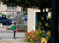 A woman walks with her baby in The Ivy Apartments in the Vickery Meadow neighborhood.(Nathan Hunsinger/Staff Photographer)