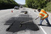 Dallas Street Services employee Gary Langley works to fix a road on Harry Hines Boulevard.(File Photo/Staff)