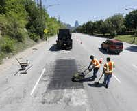 Dallas Street Services employees Gary Johnson, center, and Gary Langley, right, work to fix part of a deteriorated Harry Hines Boulevard in Dallas on April 15, 2015.(Michael Ainsworth/Staff Photographer)