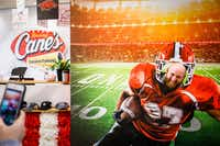 Employee Andrew Ross poses for a photo in a football display that fills the lobby at the Raising Cane's Dallas Restaurant Support Office in Plano.(Smiley N. Pool/Staff Photographer)