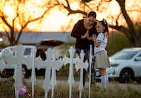 Meredith Cooper, of San Antonio, and her 8-year-old daughter, Heather, visit a memorial of 26 metal crosses near First Baptist Church in Sutherland Springs on Monday. (Jay Janner/The Associated Press)