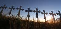 Some of the 26 crosses placed in a field are silhouetted Monday evening in Sutherland Springs to honor those who were killed in Sunday's mass shooting, when a gunman opened fire at a Baptist church in the small town southeast of San Antonio. (Louis DeLuca/Staff Photographer)