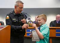 Eleven-year-old Blake Leonard of Argyle is recognized by Flower Mound Police Chief Andy Kancel during a Town Council meeting on Nov. 06, 2017.  Blake and his father, Michael, turned in a bag of money and checks, worth $4,000, that Blake had found in Flower Mound. (Michael Ainsworth/Special Contributor)