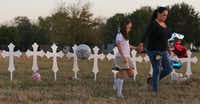 Eight-year-old Heather Cooper and her mother Meredith Cooper of San Antonio walk away after placing a remembrance at the 26 crosses placed in a field in Sutherland Springs, Texas to honor those who were killed in Sunday's mass shooting.(Louis DeLuca/Staff Photographer)