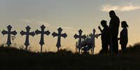 Irene and Kenneth Hernandez and their daughter Miranda Hernandez say a prayer in front of some of the 26 crosses placed in a field in Sutherland Springs to honor those who were killed in Sunday's mass shooting.(Louis DeLuca/Staff Photographer)