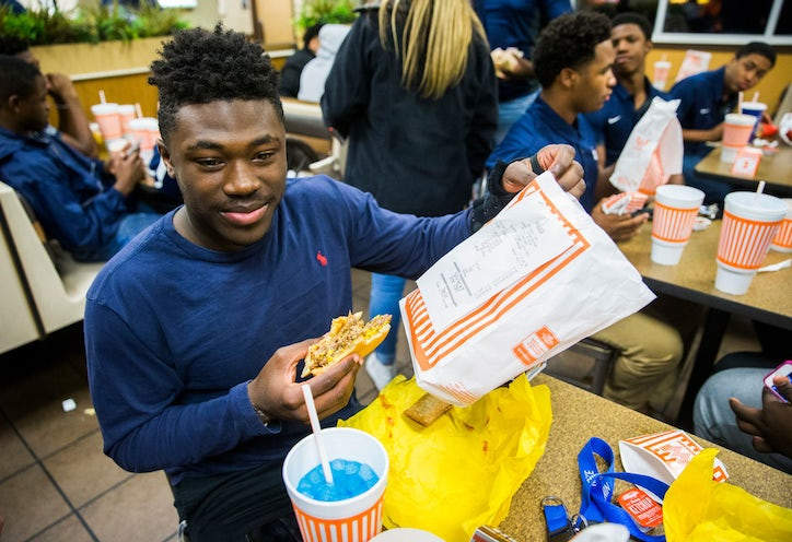 Lone Star High School Football Player Darrin Smith 16 Holds Up The Receipt For His Triple Burger With Fries As He And Classmates Celebrate Their
