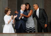 First lady Michelle Obama (center) hugs former President George W. Bush, as President Barack Obama and former first lady Laura Bush walk on stage at the dedication ceremony of the Smithsonian Museum of African American History and Culture on the National Mall in Washington on Sept. 24, 2016.(Pablo Martinez Monsivais/The Associated Press)