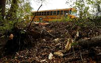 Kevin Macauley of Roper's Wrecker Service in McKinney prepares to pull the school bus out of a ravine off the southbound service road of Central Expressway north of Virginia Parkway.(David Woo/Staff Photographer)
