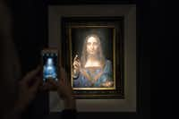 A visitor takes a photo of the painting <i>Salvator Mundi</i> by Leonardo da Vinci at Christie's New York Auction House. The coveted painting was sold at auction for $450.3 million Wednesday night.(Drew Angerer/Getty Images)
