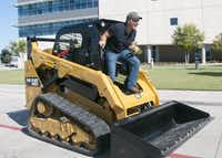 Mike Rowe, host of the television show <i>Dirty Jobs</i>, arrives in the parking lot of Dubiski Career High School in Grand Prairie on a skid-steer loader donated by Holt Cat.(File Photo/Staff)