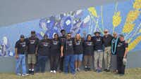 A group of ex-offenders and city of Grand Prairie staffers and volunteers pose in front of part of a mosaic tile illustration along a stretch of Interstate 30.(Tammy Chan)