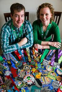 Andrew Olsen and Breanna Waldrup with some of their marathon medals.(Ashley Landis/Staff Photographer)