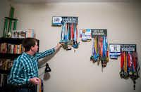 At their Irving home, Andrew Olsen looks through a collection of marathon medals from races that he and his wife, Breanna Waldrup, have run.(Ashley Landis/Staff Photographer)