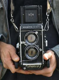 Dallas photographer Brandon Thibodeaux shows the Mamiya C330 he uses.(Louis DeLuca/Staff Photographer)