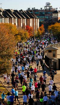 Runners filled eastbound Young Street after starting the 8-mile run during the 49th annual Dallas YMCA Turkey Trot in downtown Dallas last year.(Tom Fox/Staff Photographer)