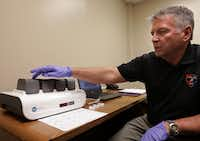 CSI and property/evidence unit manager Rick Staub runs a sample through the ParaDNA System at the Plano Police Department. (Jason Janik/Special Contributor)