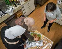 Syrian refugees Maryam Alhow, left, and Mariam Alshiblaq, center, aided by friend and interpreter Rania Stanbouly, prepare a salad at the Leah's Kitchen annual Thanksgiving Community Meal at Temple Emanu-El in Dallas on Nov. 16. (Robert W. Hart/Special Contributor)