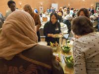Mariam Alshiblaq, a Syrian refugee, left, laughs with a guest at the Leah's Kitchen annual Thanksgiving Community Meal at Temple Emanu-El.  (Robert W. Hart/Special Contributor)