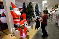A woman takes photos of artificial Christmas trees while shopping at a J.C. Penney in Seattle.(Elaine Thompson/The Associated Press)