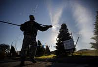 Jose Flores sprays down Noble and Douglass fir Christmas trees with water on a warm afternoon at the Optimist Tree Lot at University Drive and West Lancaster Avenue in Fort Worth. Though supplies of trees may be fewer in number this year, there should still be plenty to go around in Dallas-Fort Worth.(DMN file photo<div><br></div>)