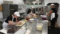 <p>In the kitchen, executive baker&nbsp;Judé Routh (left) and the staff&nbsp;stay busy making kolaches at Zamykal Gourmet Kolaches on Keller Springs Road. They make 600 kolaches a day — or 900 on busy days. (Louis DeLuca/Staff Photographer)</p>