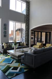 Work for the ground up, says Elaine Williamson-Romero. She layered in the color and color with a bright geometric rug in this living room.