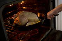 Rebecca White places a cast iron pan with a whole chicken in it into an oven Thursday, April 14, 2016 in Plano, Texas. (G.J. McCarthy/The Dallas Morning News)(G.J. McCarthy/Staff Photographer)