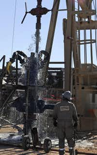 Water gushes out of a drilling pipe as it is pulled up to be replaced with a fresh pipe at a hydraulic fracturing site in Midland in 2013. The drilling method known as fracking uses huge amounts of high-pressure, chemical-laced water to free oil and natural gas trapped deep in underground rocks.(Pat Sullivan/The Associated Press)