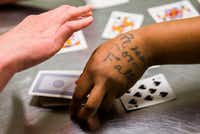"""Rise or Fall"" is tattooed on the hand of inmate Sheniqua Miller as she and Stacy Jensen play cards in their unit at Burnet County Jail. Miller had probation but violated the terms, testing positive for marijuana. (Ashley Landis/Staff Photographer)"