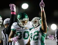Saskatchewan Roughriders' Cameron Marshall (right) celebrates a touchdown with Spencer Moore against the Calgary Stampeders during the second half of a Canadian Football League game in October.(Jeff McIntosh/The Associated Press)