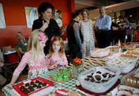 Sisters Belle Hartgrove (center), 5,  and  Luna Hartgrove, 7,  of Dallas check out the competition after turning in their two entries in the new Kids' Choice category during the 22nd annual The Dallas Morning News-Central Market Holiday Cookie Contest at Central Market on Lovers Lane in Dallas Nov. 2, 2017. (Andy Jacobsohn/Staff Photographer)