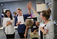 Susan O'Brien (left) of Hail Merry, watches as Charlsie Doan (second from left), a student judge, gives a high-five to Rebecca White (right) of A Pleasant Little Kitchen, as Pam Nicholson reaches for a cookie while they judge the 22nd annual The Dallas Morning News-Central Market Holiday Cookie Contest at Central Market on Lovers Lane in Dallas Nov. 2, 2017. (Andy Jacobsohn/Staff Photographer)