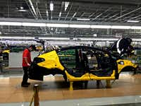 Workers assemble the Forte sedan on the floor of a Kia plant in Nuevo Leon, Mexico, which began production in May. (Natalie Kitroeff/Tribune News Service)