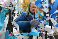 Karen Rosenkrans of Dallas ties a ribbon on a memorial in honor of her father, who served in the Army during World War II, as she attends a Pearl Harbor remembrance held at Thanks-Giving Square in downtown Dallas on Thursday, December 7, 2017. (Louis DeLuca/The Dallas Morning News)(Louis DeLuca/Staff Photographer)