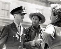 Before deploying overseas in World War II, James Stewart visited his friend Henry Fonda on the set of <i>The Ox-Bow Incident</i>. They are photographed speaking with director William Wellman. (Leonard Maltin collection)