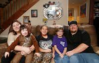 From left: Tommie Ogletree holding Zachary Ogletree, 3; Sydney Ogletree, 12; Bradley Ogletree, 10; and Kelley Ogletree in their home this month in Lewisville. Zachary, who was diagnosed with severe autism as a baby, is one of 8,000 Denton County kids enrolled in the Children's Health Insurance Program.(Vernon Bryant/Staff Photographer)