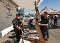 Fort Worth Police officers J.M. Aguilar (left) and R. Delos Santos collect weapons during a gun buyback program on Saturday.(Special Contributor/Rex C. Curry)
