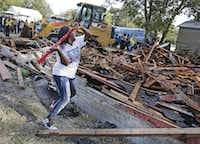 "Cynthia King, Shavon Randle's great-aunt, puts the finishing whacks on ""this godforsaken house"" where the girl's body was found. Relatives and neighbors gathered for the demolition of the run-down structure on Kiest Boulevard in October.(Louis DeLuca/Staff Photographer)"