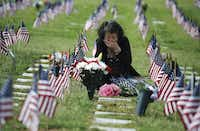 Una Pemberton of Wichita Falls weeps at the grave of her son, Clem J. Strait III, who served in the Army in the Persian Gulf War. She was there to honor him during the Memorial Day observance at D-FW National Cemetery.(David Woo/Staff Photographer<div><br></div><div><br></div><div><br><div><br></div><div><br></div><div><br></div></div>)