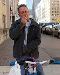 Sean Baugh lights a cigarette as he talks about his dog Lamb of God after a hearing at Dallas Municipal Court in downtown Dallas on Monday. The dog is accused of biting three times, including a 13-year-old boy last month. The dog is scheduled to die, but Dallas Judge Michael Acuna is weighing whether to grant the dog a rehearing.(Irwin Thompson/Staff Photographer)