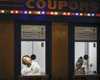 With no guests in sight near 10 p.m., Brandy Mosley dozes off at the end of a 12-hour shift in her State Fair coupon booth. On weeknights, the entrance gates close at 9 p.m., but the ticket booths and Midway stay open for a little longer.(Smiley N. Pool/Staff Photographer)