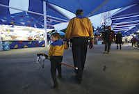 James Stephen La Due rides his stick horse as his dad, Stephen Ladue of Mansfield, guides the 4-year-old through the midway.(Nathan Hunsinger/Staff Photographer)