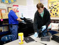 David Withrow (left) and Andrew Wilson with the IT department clean laptops in the classrooms of Sunnyvale Middle School The school district has been hit by flu and is shut down today and tomorrow (Nathan Hunsinger/The Dallas Morning News)(Nathan Hunsinger/Staff Photographer)
