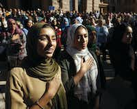 Hiba Loya and Donia Kased, both of Houston, join in the singing of the national anthem outside the Texas Capitol during the Texas Muslim Capitol Day rally in Austin in January.(Vernon Bryant/Staff Photographer)