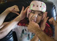 Kara Zartler punches herself in the head as her father, Mark, places a medical mask over her nose and mouth and fills it with marijuana vapor in an effort to control her fit of self-abuse. Her parents sought to legalize marijuana for autistic patients in Texas.(Smiley N. Pool/Staff Photographer)