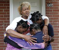 Paula Wooten prays with her grandchildren A'avryanna Wooten (left), 10, I'ivryanna Wooten (center), 9, and R'reanna Wooten, 11, in front of their Dallas Housing Authority apartment before they walk to school at George W. Carver Creative Arts Learning Center.(David Woo/Staff Photographer)
